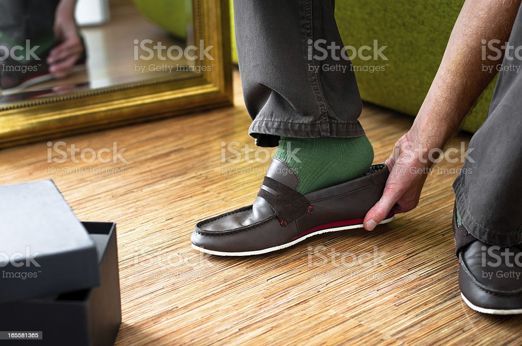 Close-up of man trying on new moccasins shoes, wardrobe interior stock photo