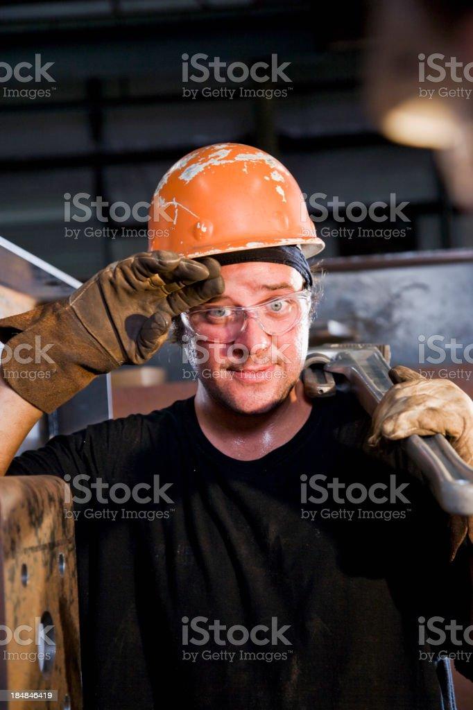 Closeup of man wearing hardhat working hard in factory stock photo