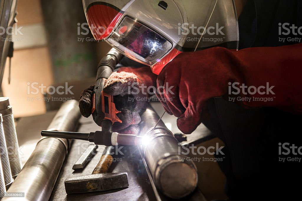 Closeup of man wearing mask welding in a workshop stock photo