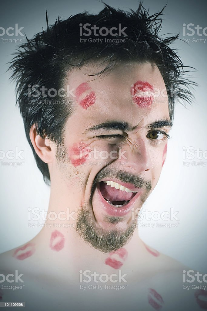 Close-up of man's face winking, covered in lip stick marks stock photo