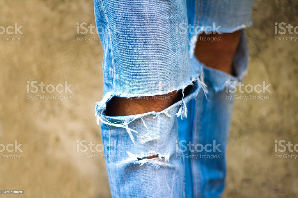 Close-up of Man's Fashionably Shredded-at-the-Knee Blue Jeans stock photo