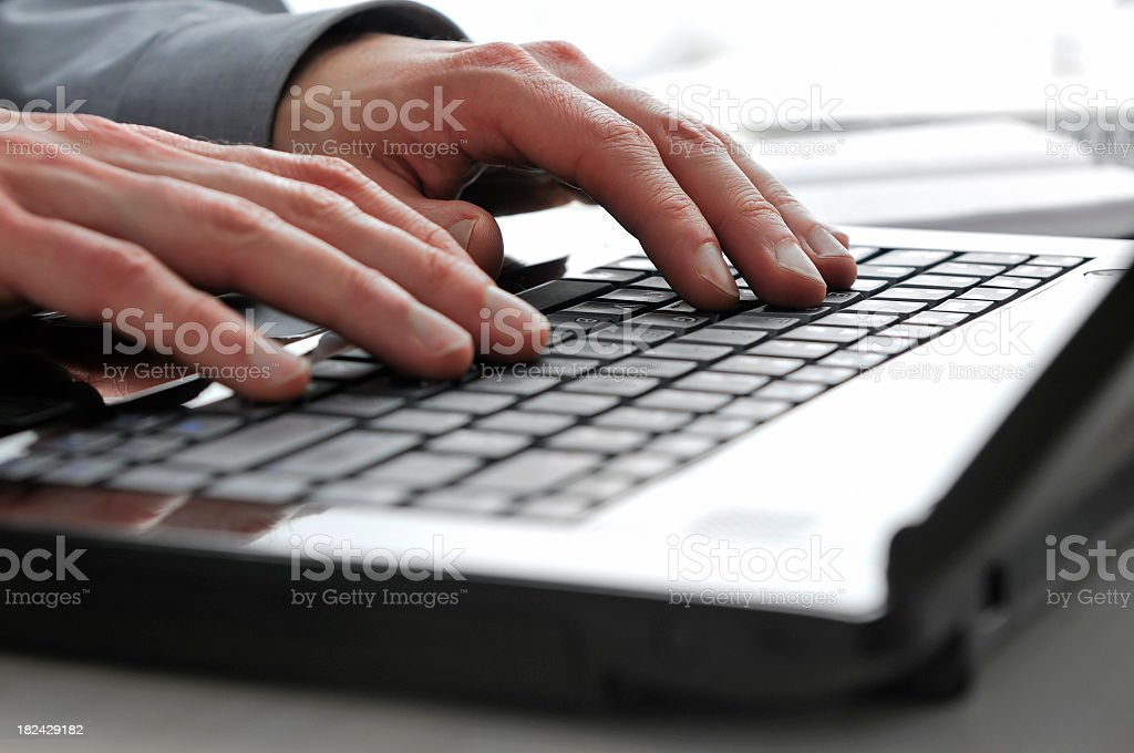 Close-up of man's fingers typing on modern, shiny, black laptop royalty-free stock photo