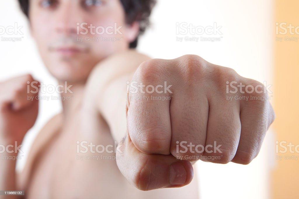 Close-Up of Man's Fist Punching Camera - POV royalty-free stock photo