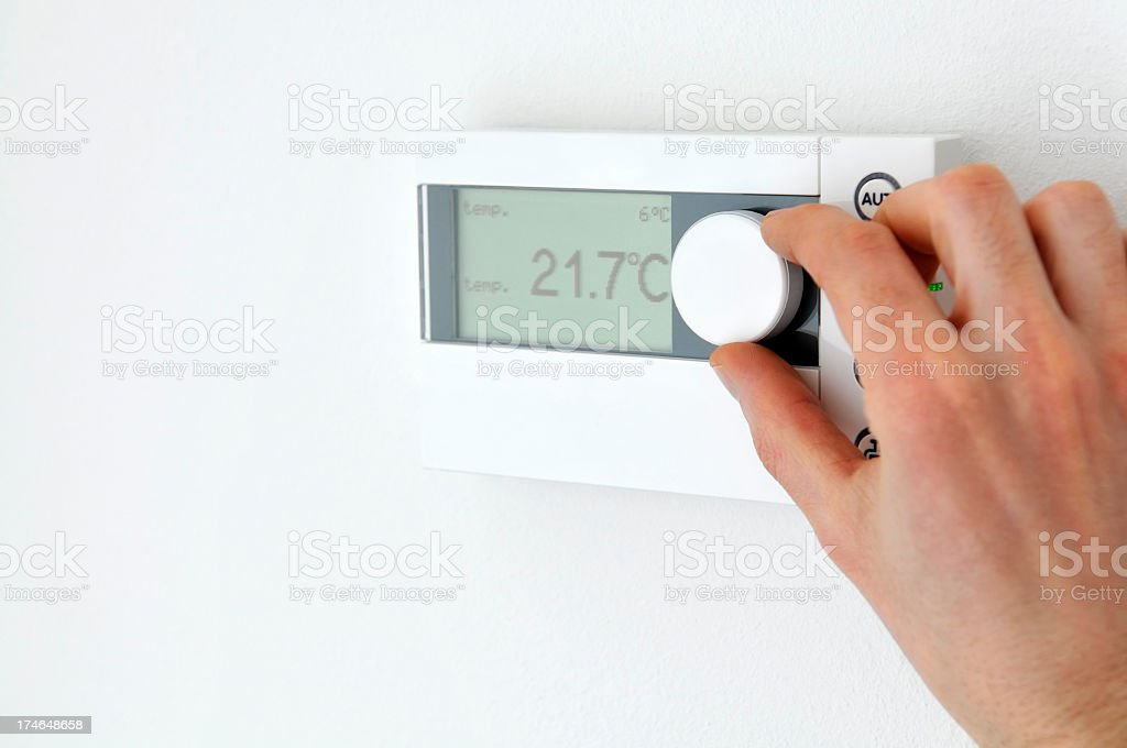 Close-up of man's hand adjusting an electronic thermostat, home interior royalty-free stock photo
