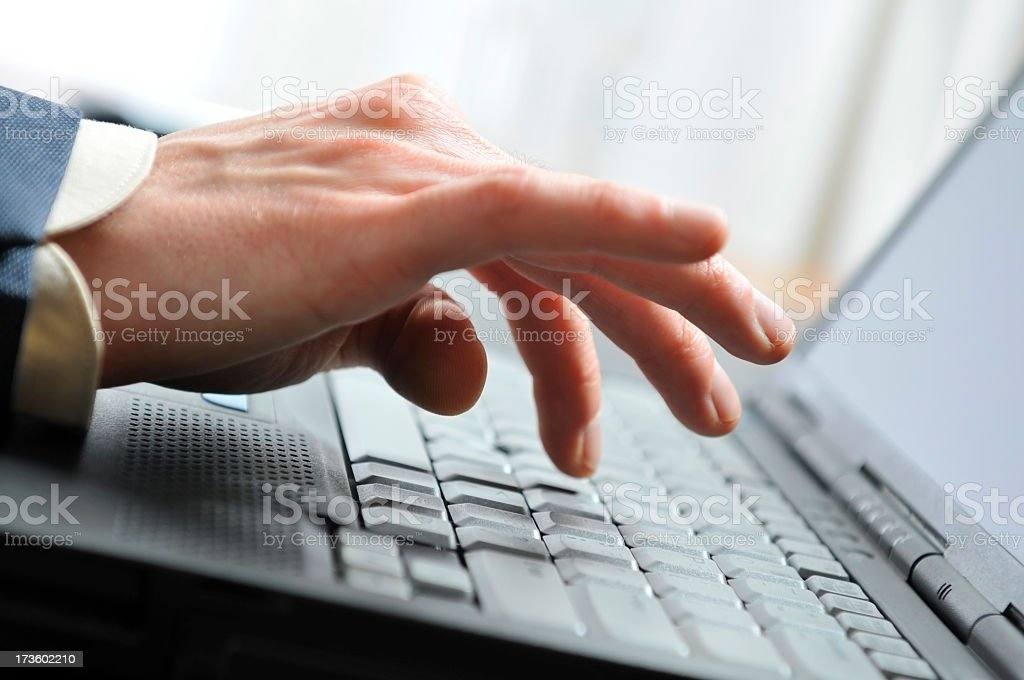 Close-up of man's hand inputing data on the laptop royalty-free stock photo