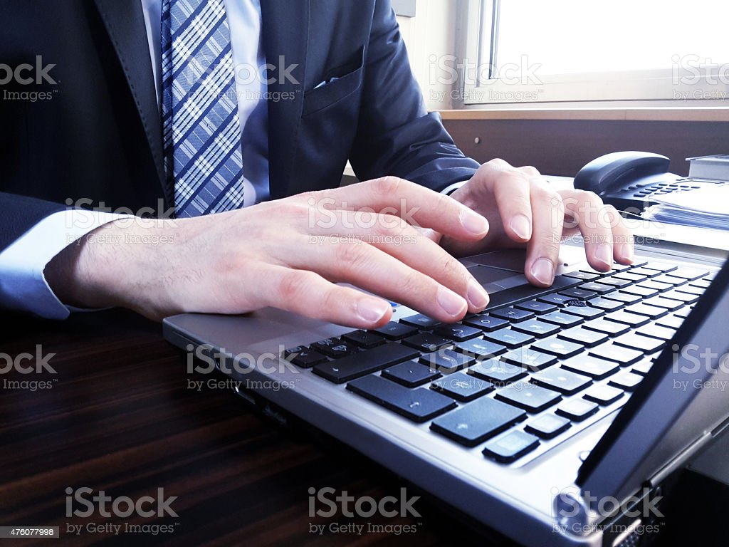 Close-up of man's hand inputing data on the laptop stock photo