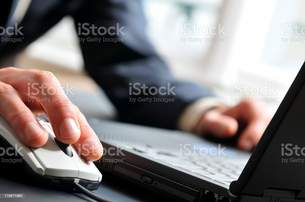 Close-up of man's hand on computer mouse, working on laptop royalty-free stock photo