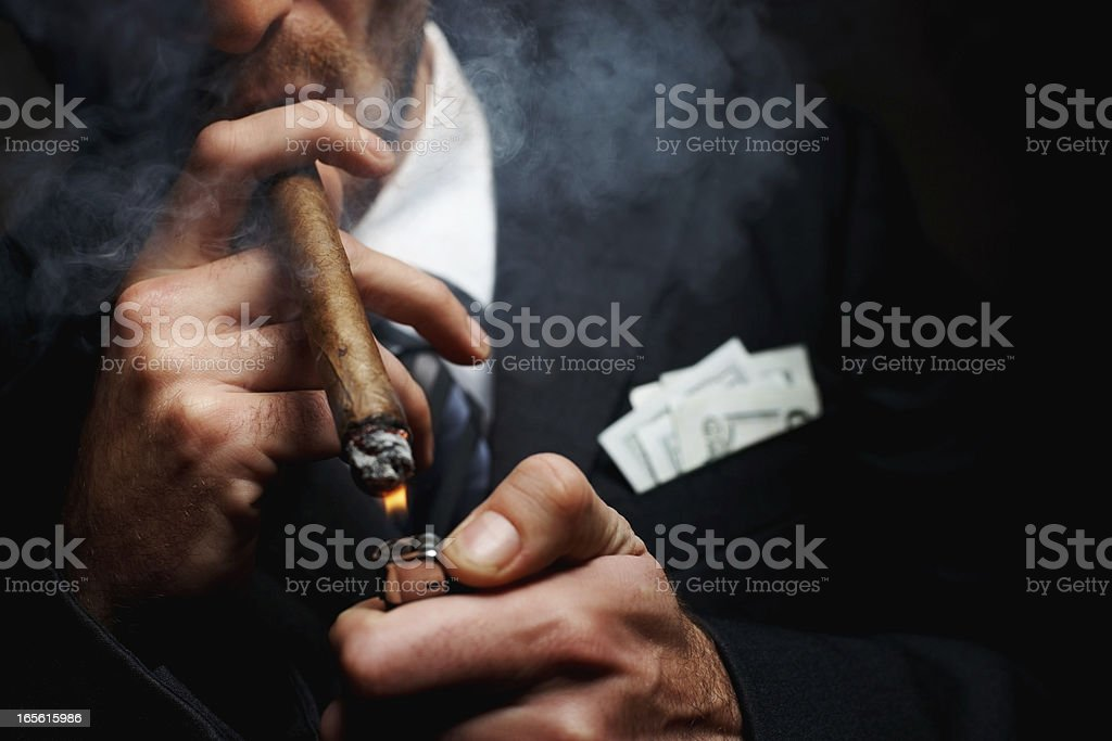 Close-up of man's hand with cigar and lighter stock photo