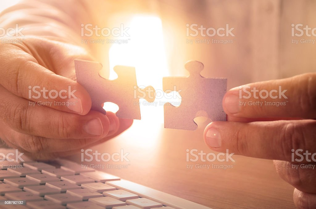 Closeup of man's hands holding puzzle pieces stock photo