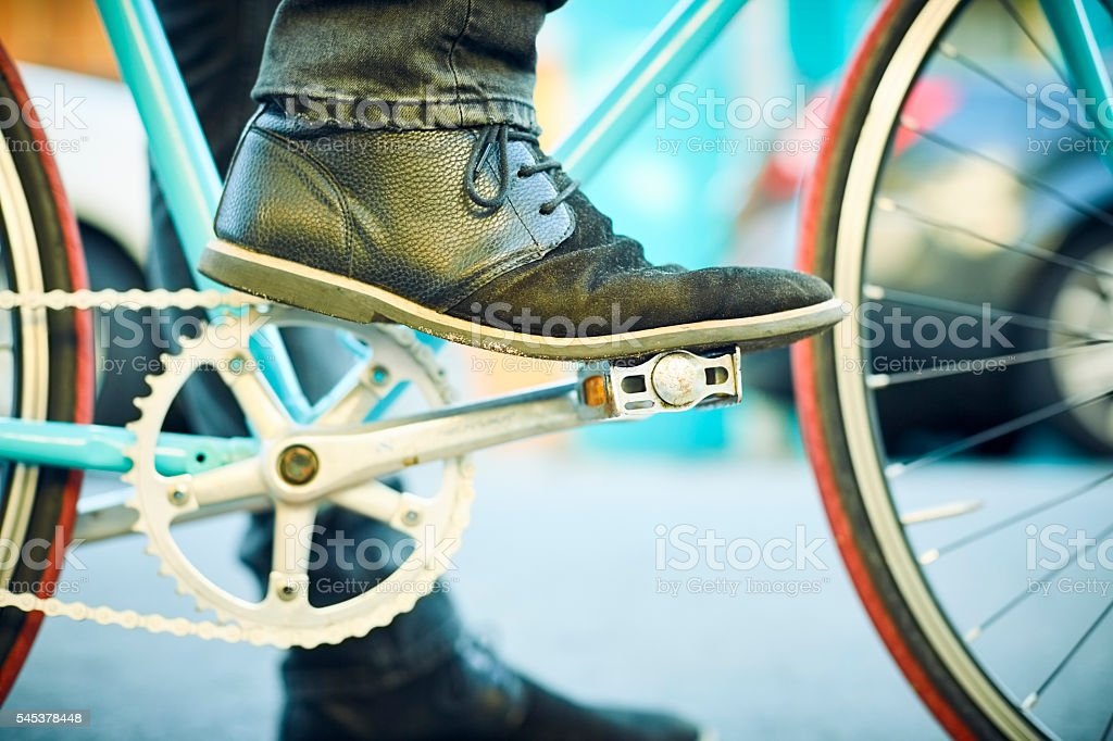 Close-up of man's leg on bicycle pedal stock photo