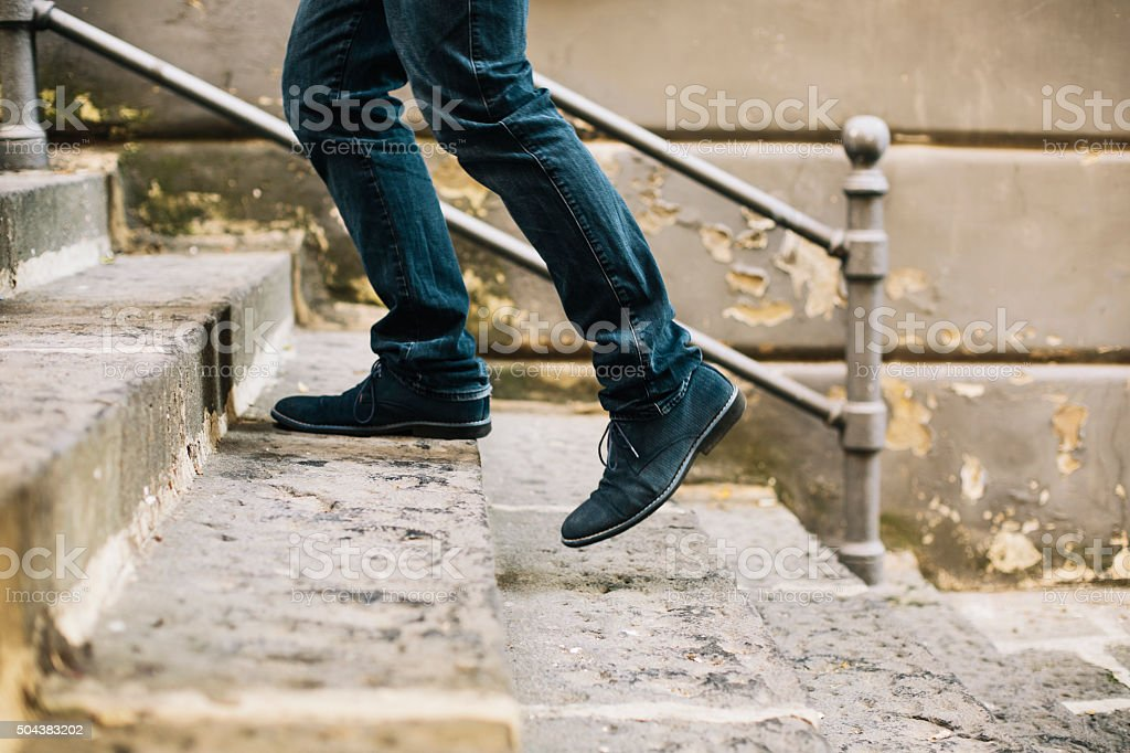 Close-up of man's shoes walking upstairs stock photo