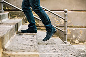 Close-up of man's shoes walking upstairs