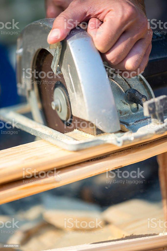 Closeup of manual worker using circular saw stock photo