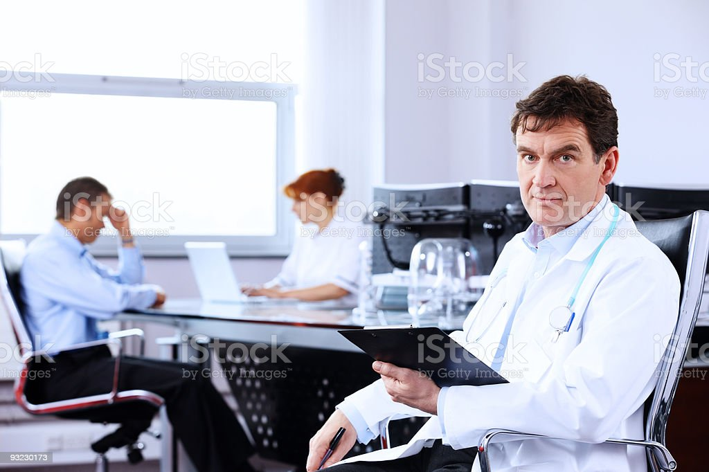 close-up of mature Doctor sitting in modern office with colleagues royalty-free stock photo