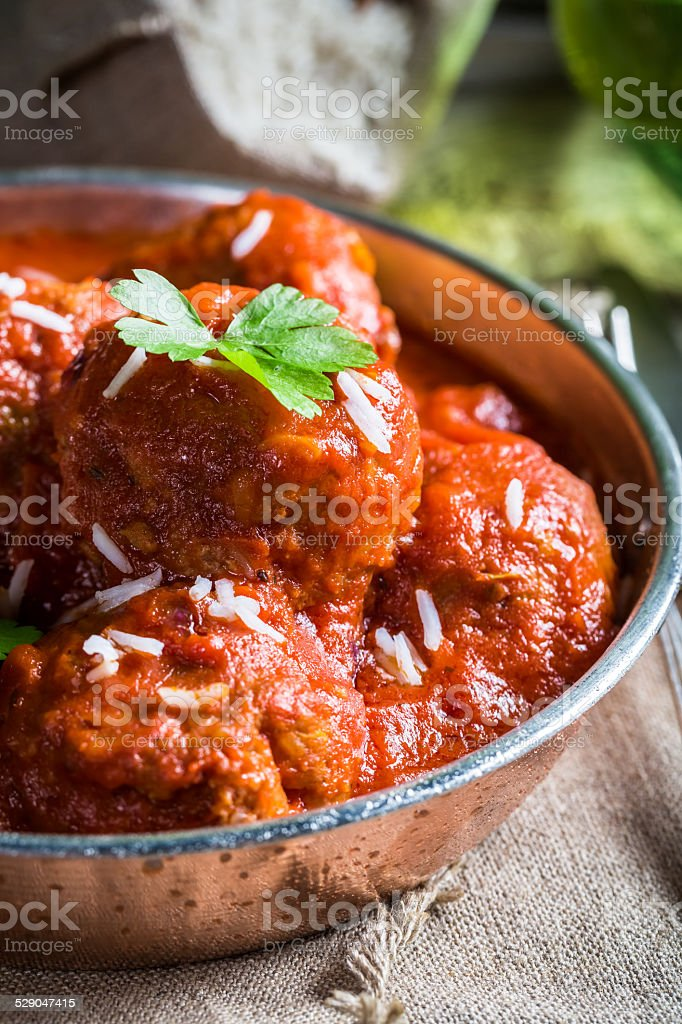 Closeup of meatballs in tomato sauce with parsley stock photo