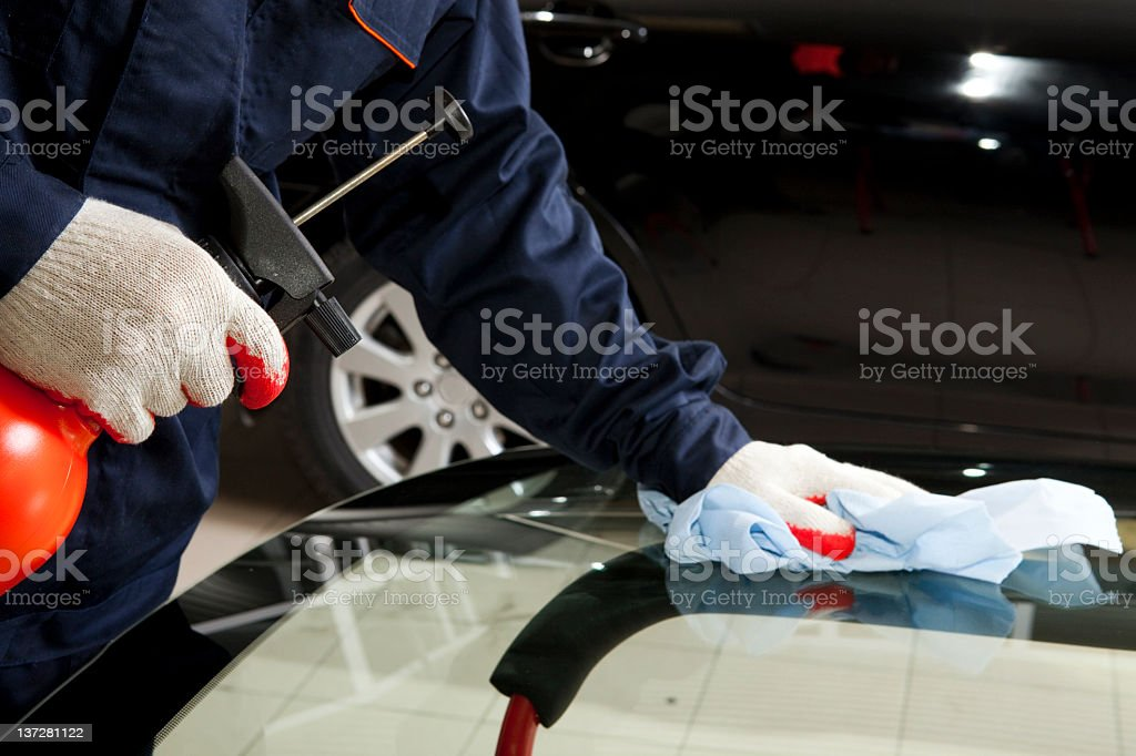 Close-up of mechanic cleaning glass in auto repair shop royalty-free stock photo