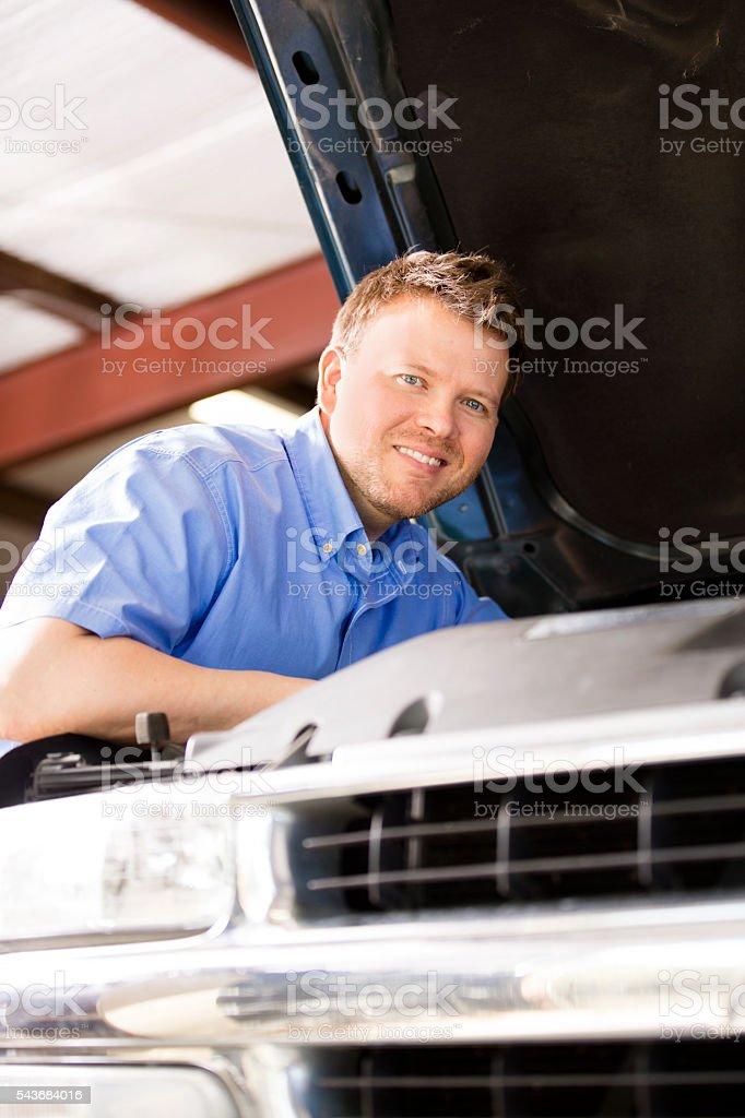 Close-up of mechanic working on vehicle engine. Repair shop. stock photo