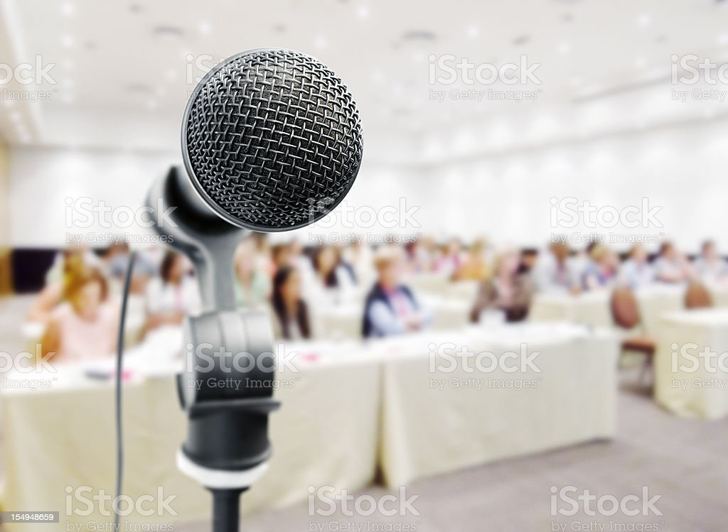 Closeup of microphone against blurry auditorum royalty-free stock photo