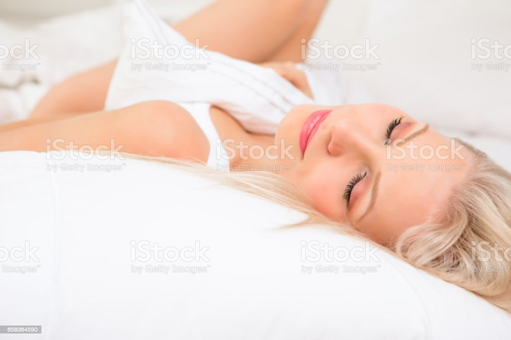 Close-up of mid adult model sleeping on bed stock photo