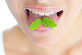 Close-up of mint leaves on a woman's tongue