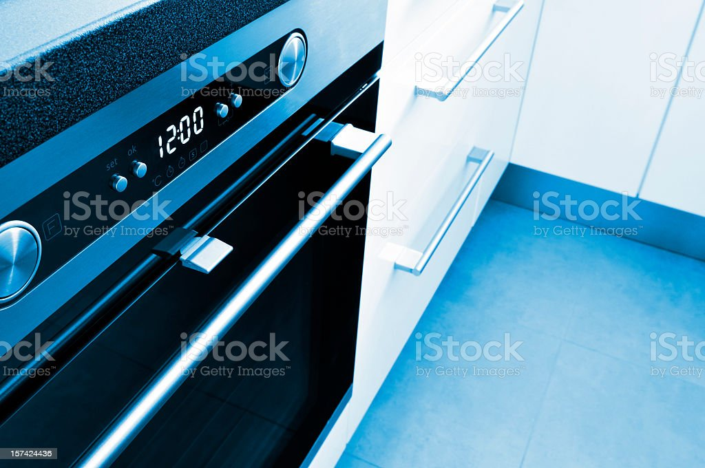 Close-up of modern oven, white cabinets, kitchen interior, blue toned stock photo