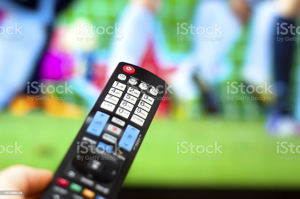 Close-up of modern remote control, watching soccer game on TV stock photo