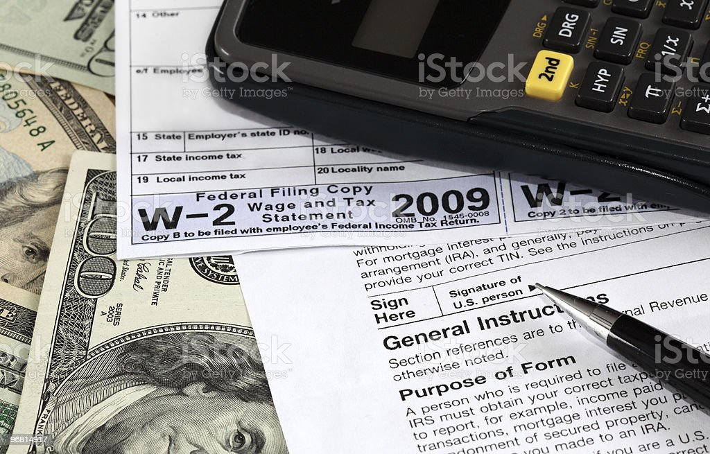 A close-up of money, a calculator and a W-2 form stock photo
