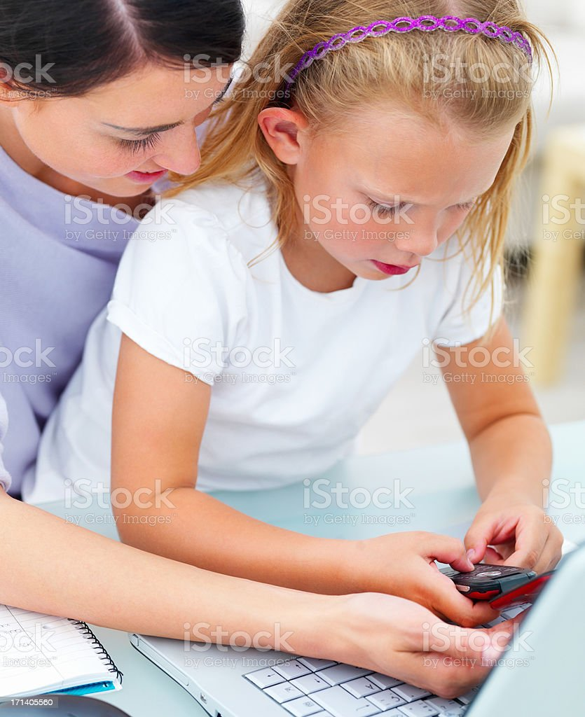 Closeup of mother and daughter holding mobile phone stock photo