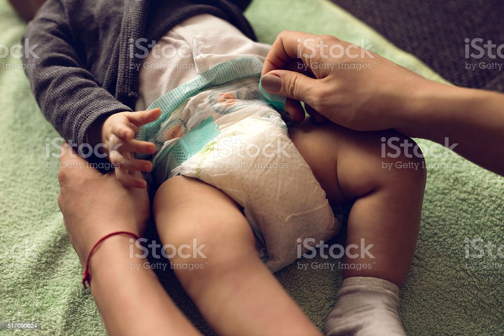 Close-up of mother changing baby's diaper. stock photo