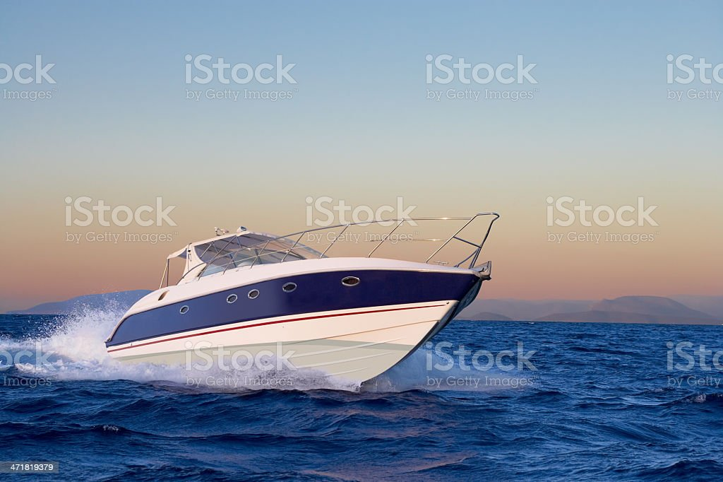 Close-up of motorboat sailing in ocean at sunrise stock photo