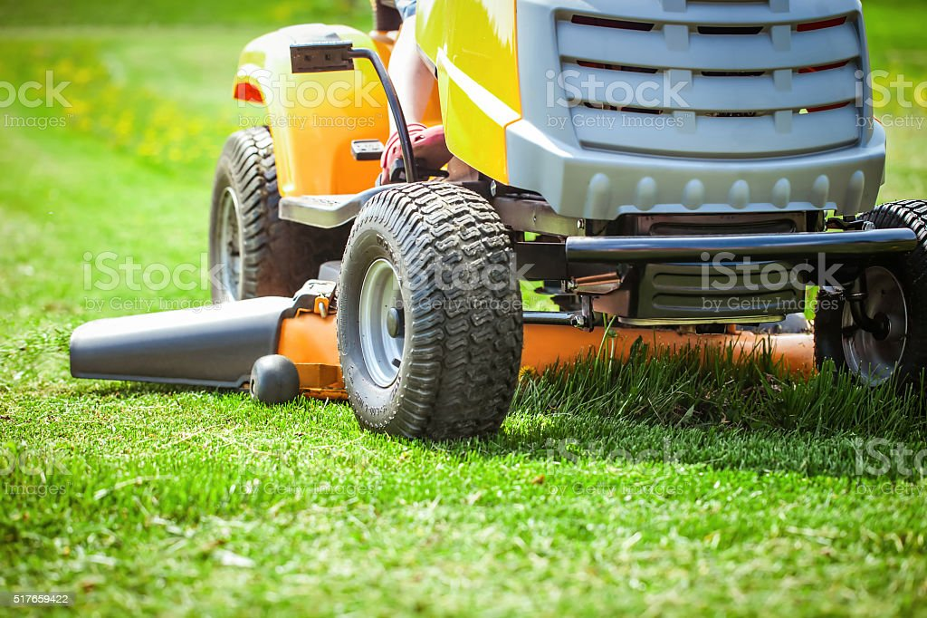 Closeup of mower cutting the grass stock photo