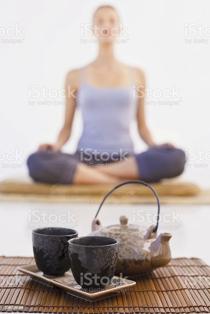 Closeup of mug and kettle with woman background stock photo