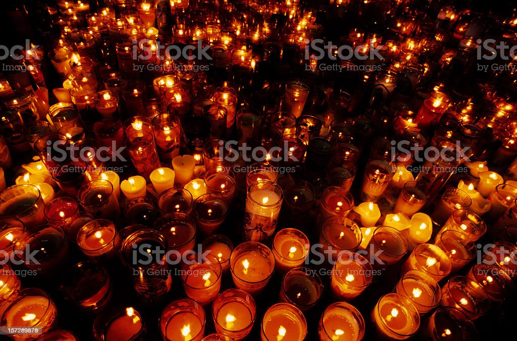 A close-up of multiple candles in a vigil stock photo