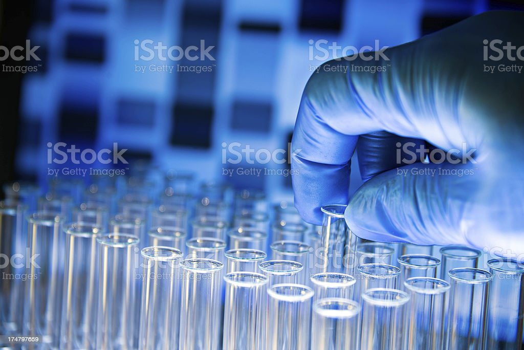 Close-up of multiple test tubes and a gloved hand removing 1 royalty-free stock photo