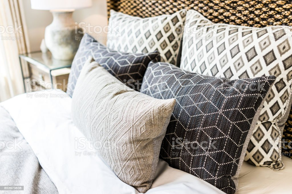 Closeup of new bed comforter with decorative pillows, headboard in...
