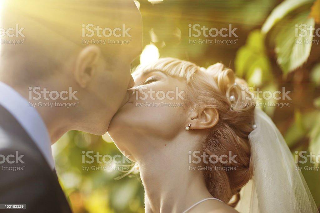 Gros plan de couple de jeunes mariés embrassant dans la lumière du soleil photo libre de droits