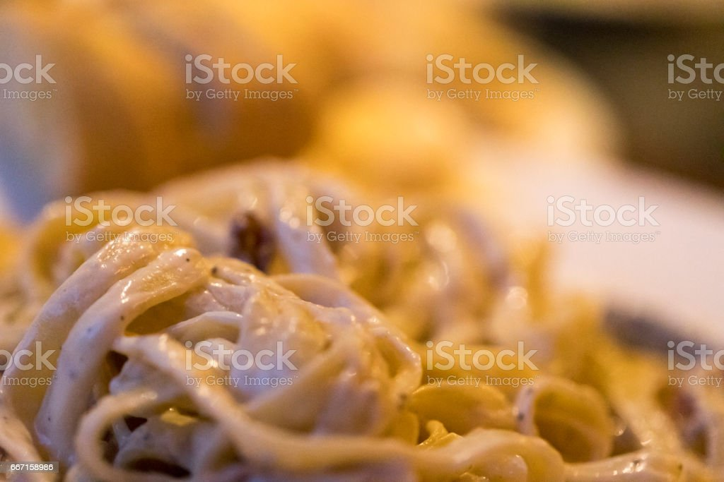 Close-up of of pasta alla carbonara with fettucine and its creamy sauce and bacon, with slices of bread visible in the bokeh. stock photo