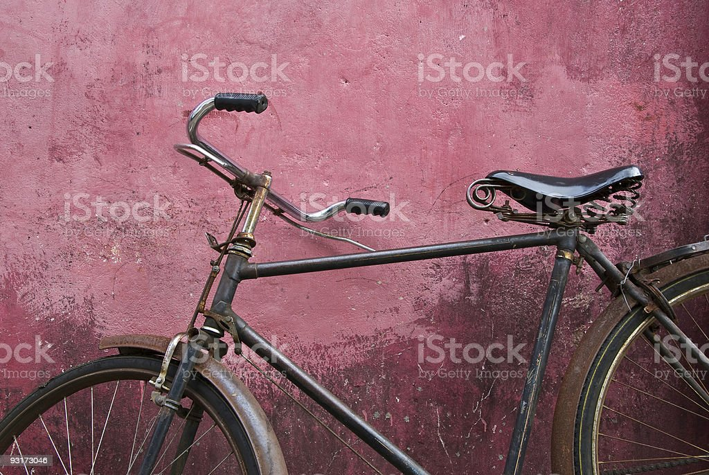Close-up of old black bicycle leaning against pink wall stock photo