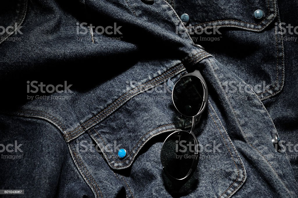 Close-up of old denim jacket with sunglasses stock photo