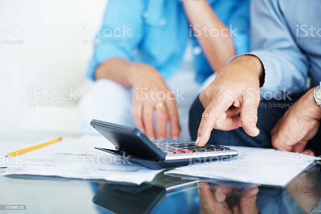 Closeup of old man's hand calculating bills at home stock photo