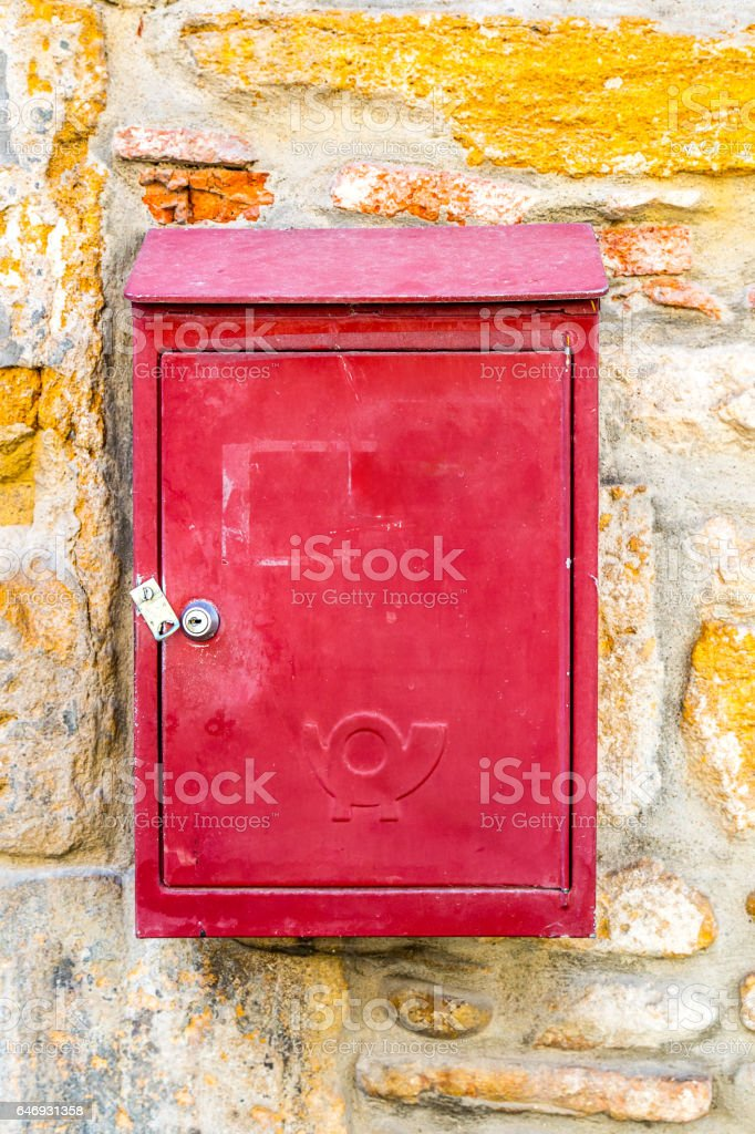 Close-up of old metallic mail post letter box colored in vibrant red attached on ancient stone wall with posthorn common sign stock photo