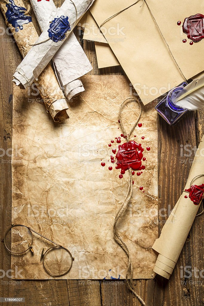 Closeup of old scrolls and sealing wax on wooden table royalty-free stock photo