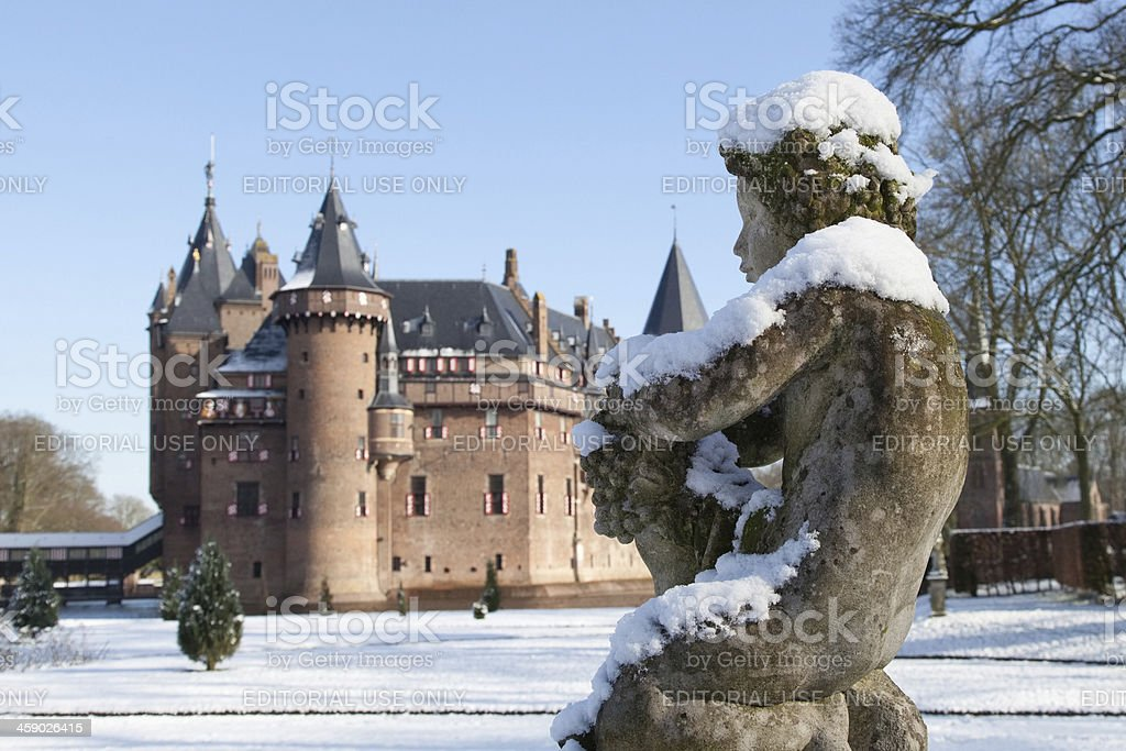 Close-up of old snow-covered statue with castle in background stock photo