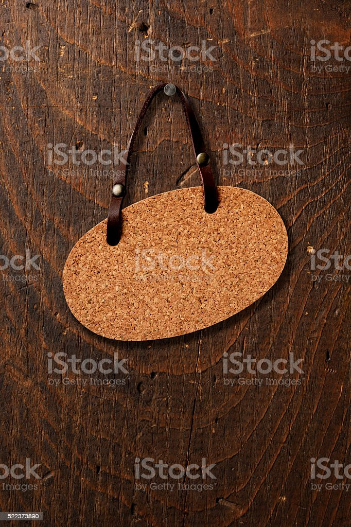 Close-up of old wooden door hanging a blank corkboard sign stock photo