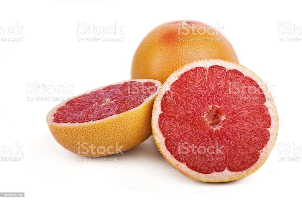 Close-up of one sliced and one full grapefruit royalty-free stock photo