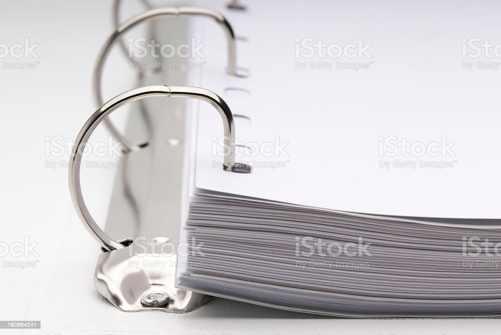 Close-up of open white binder full of white blank paper stock photo