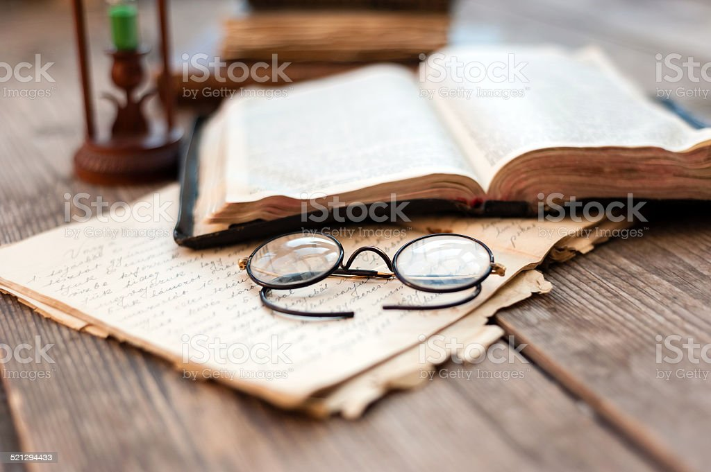Close-up of opened book pages and glasses stock photo