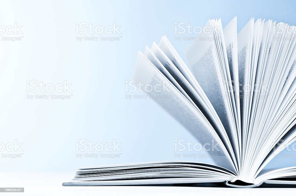 Close-up of opened book with pages on light blue background royalty-free stock photo
