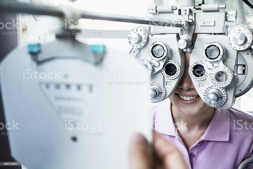 Close-up of optometrist doing an eye exam on young woman stock photo