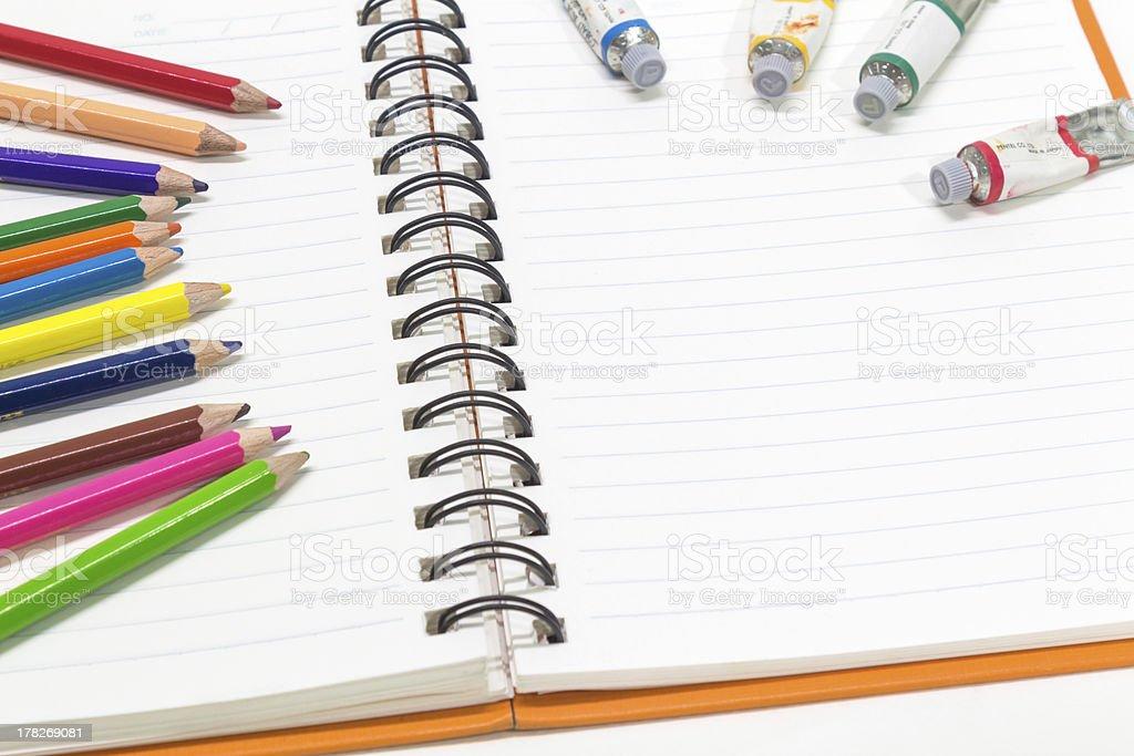 Close-up of orange Примечание книга и цветные карандаши, водных тонах Стоковые фото Стоковая фотография
